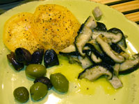 On the plate with a few olives and yellow tomato